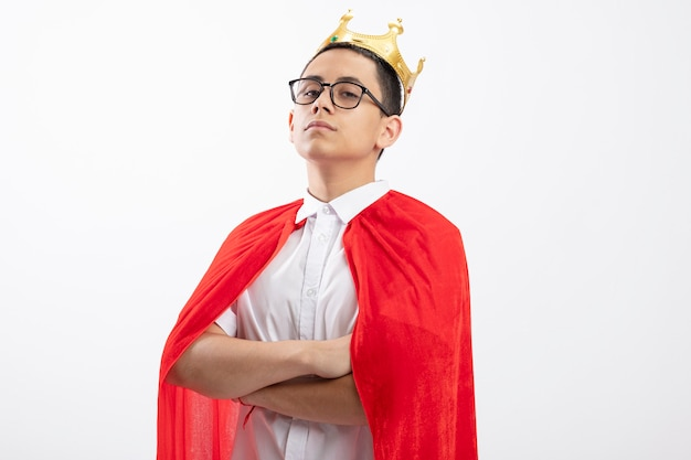 Confident young superhero boy in red cape wearing glasses and crown standing with closed posture looking at camera isolated on white background with copy space