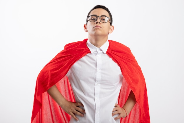 Confident young superhero boy in red cape wearing glasses looking at camera keeping hands on waist isolated on white background
