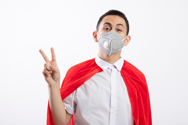Confident young superhero boy in red cape wearing protective mask doing peace sign looking at camera isolated on white background