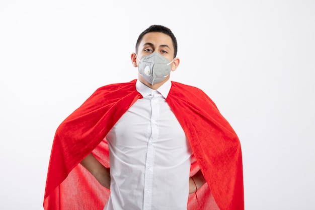 Confident young superhero boy in red cape wearing protective mask keeping hands on waist looking at camera isolated on white background