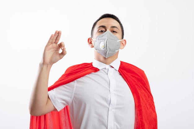 Confident young superhero boy in red cape wearing protective mask looking at camera doing ok sign isolated on white background