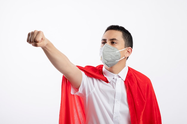 Confident young superhero boy in red cape wearing protective mask stretching out fist looking at side isolated on white background