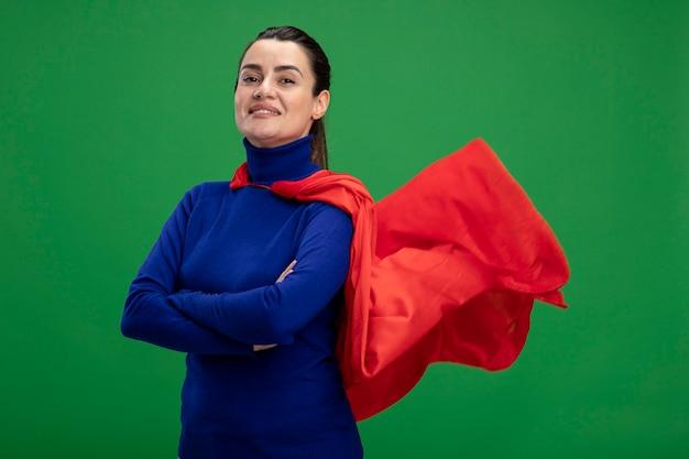 緑で隔離の手を交差する自信を持って若いスーパーヒーローの女の子
