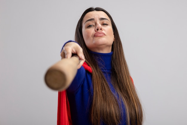 Confident young superhero girl holding out baseball bat at camera isolated on white background