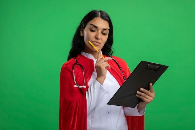 Уверенная молодая девушка супергероя смотрит вниз в медицинском халате со стетоскопом, держащим буфер обмена, кладет карандаш на щеку, изолированную на зеленом