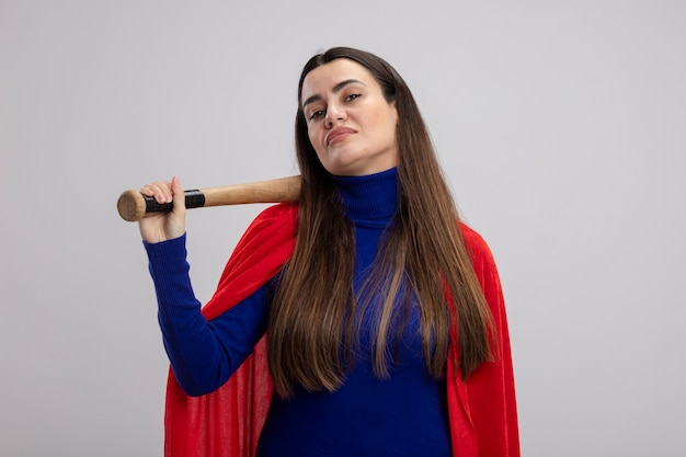 Confident young superhero girl putting baseball bat on shoulder isolated on white background