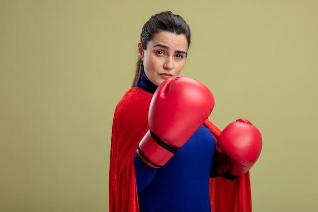 Fiduciosa giovane ragazza del supereroe che indossa guantoni da boxe in piedi nella posa di combattimento isolata su verde oliva