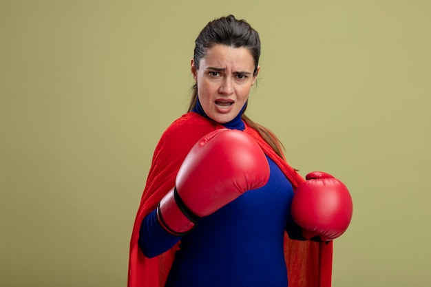 올리브 그린에 고립 된 포즈 싸움에 서 권투 장갑을 끼고 자신감 젊은 슈퍼 히어로 소녀