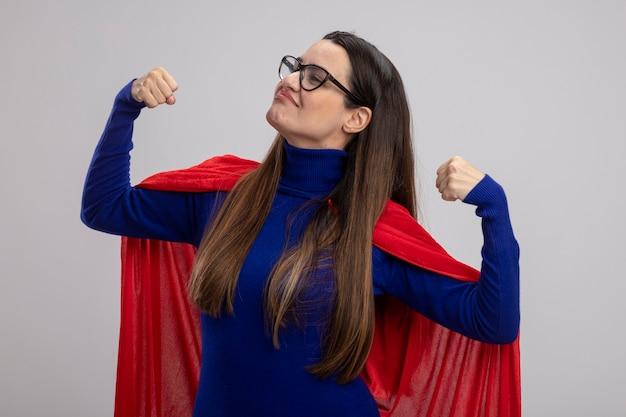 포즈를 싸우고 흰색에 고립 된 강한 제스처를 보여주는 안경을 쓰고 자신감이 젊은 슈퍼 히어로 소녀