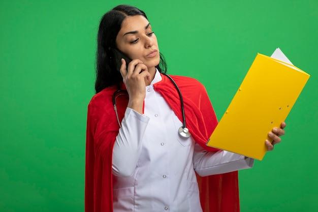 청진기를 들고 폴더를보고 의료 가운을 입고 자신감이 젊은 슈퍼 히어로 소녀는 녹색에 고립 된 전화에 말한다