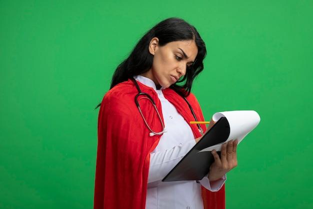 Уверенная молодая девушка супергероя в медицинском халате со стетоскопом, держащая и пишущая что-то в буфере обмена, изолированном на зеленом