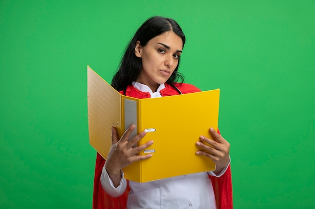 Confident young superhero girl wearing medical robe with stethoscope holding folder isolated on green