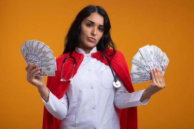 Fiduciosa giovane ragazza del supereroe che indossa abito medico con lo stetoscopio che tiene soldi isolati sulla parete arancione
