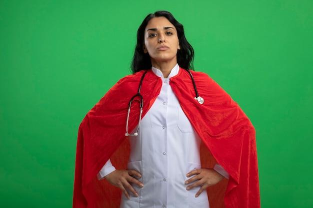 緑の壁に隔離された腰に手を置く聴診器で医療ローブを身に着けている自信を持って若いスーパーヒーローの女の子