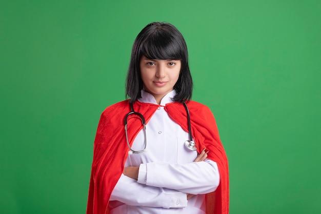 의료 가운과 녹색에 고립 된 망토 횡단 손으로 청진기를 입고 자신감 젊은 슈퍼 히어로 소녀