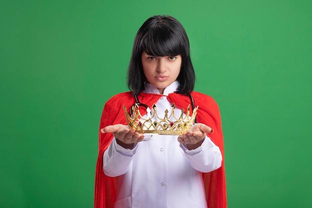 緑に分離されたクラウンを保持している医療ローブとマントと聴診器を身に着けている自信を持って若いスーパーヒーローの女の子