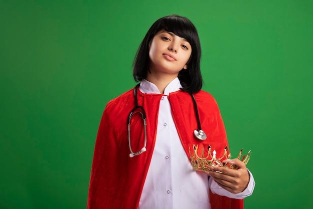 Fiduciosa giovane ragazza del supereroe che indossa uno stetoscopio con abito medico e mantello che tiene corona