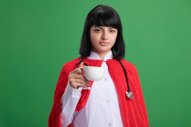 Fiduciosa giovane ragazza del supereroe che indossa uno stetoscopio con abito medico e mantello che tiene tazza di tè isolato su verde