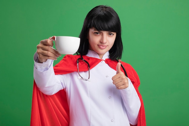 Confident young superhero girl wearing stethoscope with medical robe and cloak holding cup of tea showing thumb up isolated on green wall