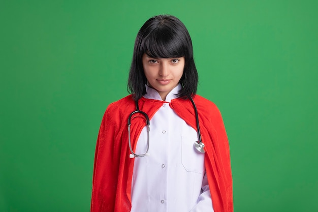 Confident young superhero girl wearing stethoscope with medical robe and cloak isolated on green