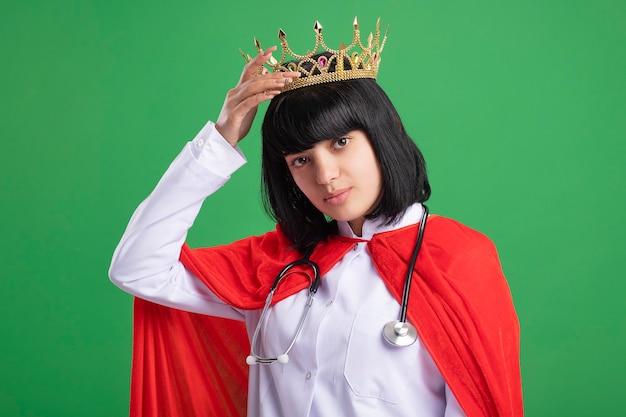 Fiduciosa giovane ragazza del supereroe che indossa uno stetoscopio con abito medico e mantello mettendo la corona sulla testa isolata sul verde