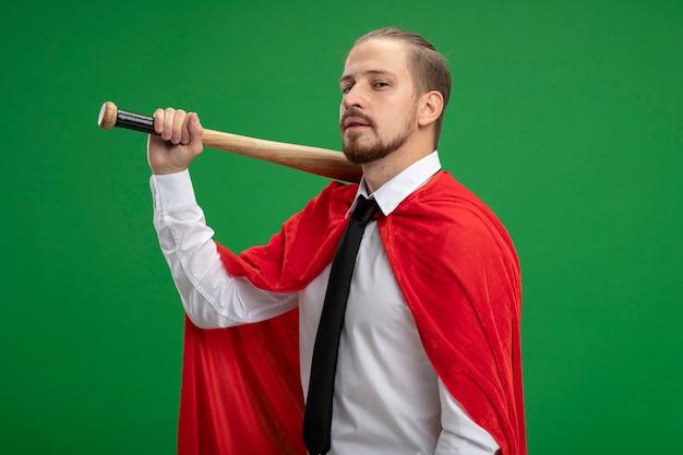 Confident young superhero guy holding baseball bat on shoulder isolated on green background