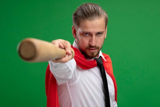 녹색 배경에 고립 된 카메라에서 야구 방망이를 들고 자신감 젊은 슈퍼 히어로 남자