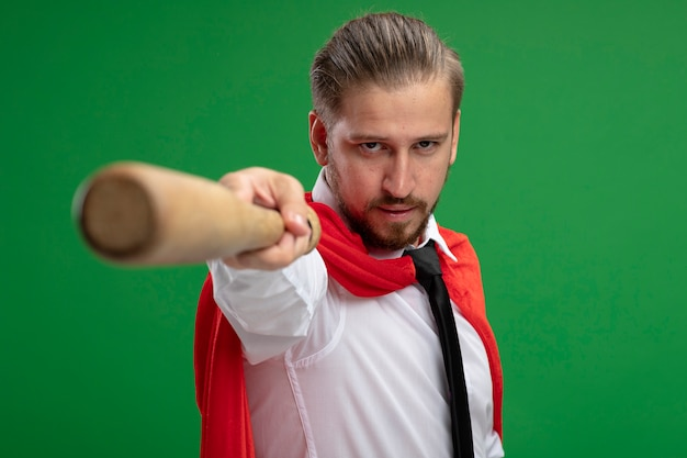 Confident young superhero guy holding out baseball bat at camera isolated on green background