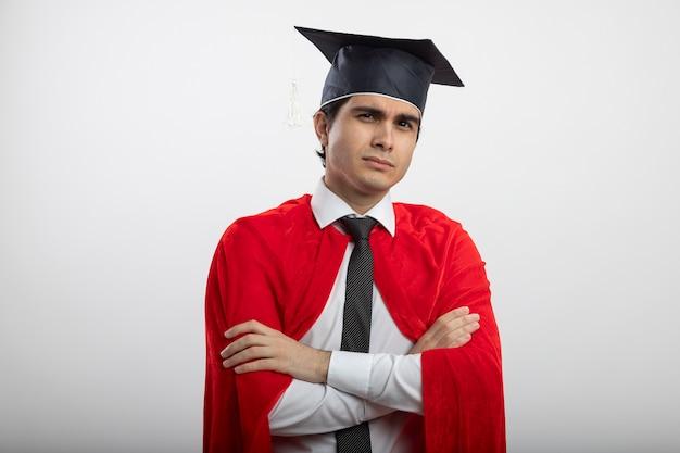 ネクタイと卒業生の帽子の交差する手を身に着けているカメラを見て自信を持って若いスーパーヒーローの男