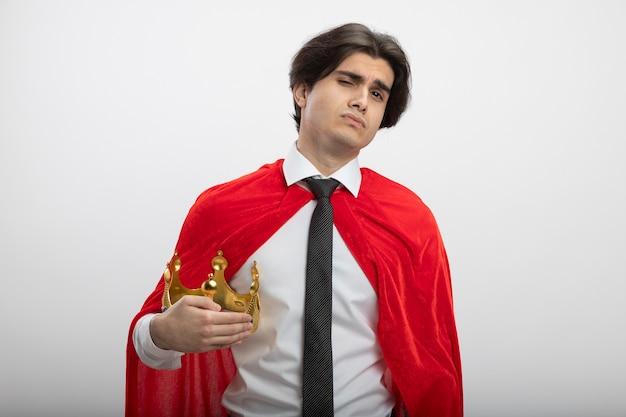 Уверенный молодой парень супергероя смотрит в камеру в галстуке, держа корону на белом фоне