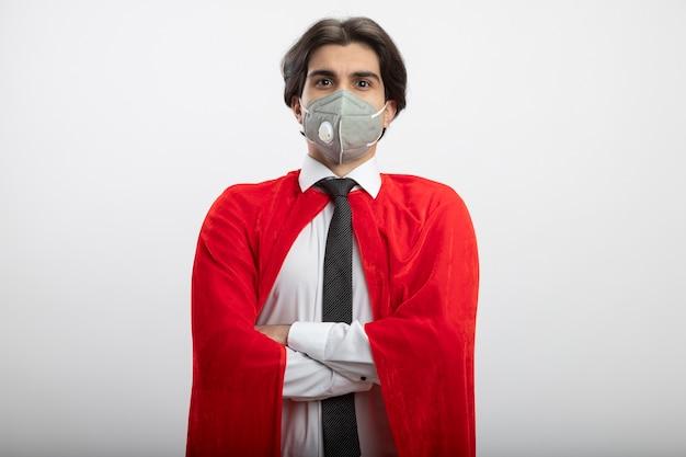 Ragazzo giovane supereroe sicuro che guarda l'obbiettivo che indossa cravatta e maschera medica