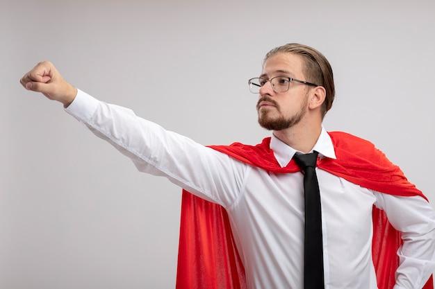 Fiducioso giovane supereroe ragazzo guardando a lato indossando abito medico con lo stetoscopio e gli occhiali alzando la mano isolata su sfondo bianco