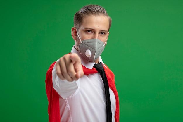 緑の背景に分離されたジェスチャーを示す医療マスクとネクタイを身に着けている自信を持って若いスーパーヒーローの男