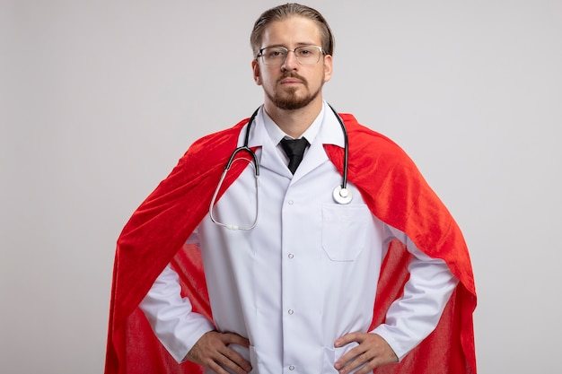 Confident young superhero guy wearing medical robe with stethoscope and glasses putting hands on hip isolated on white background