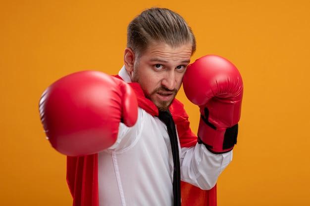 오렌지에 고립 된 포즈 싸움에 서 서 넥타이와 권투 장갑을 끼고 자신감 젊은 슈퍼 히어로 남자