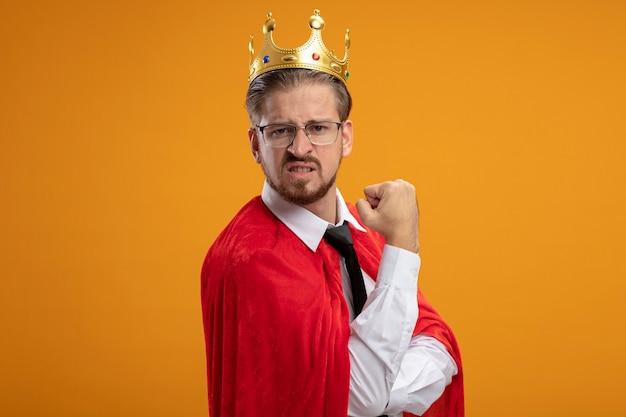 オレンジ色の背景に分離されたはいジェスチャーを示す眼鏡とネクタイと王冠を身に着けている自信を持って若いスーパーヒーローの男