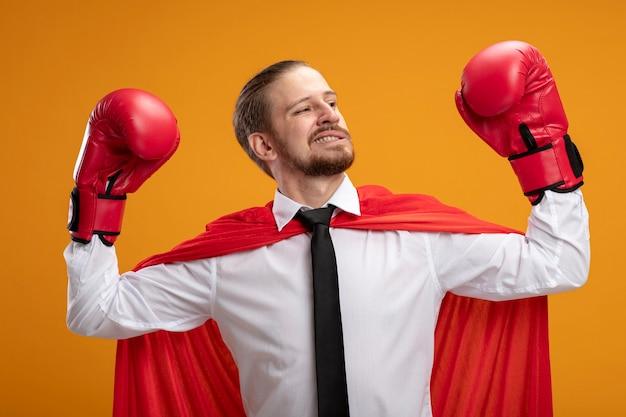 Fiducioso giovane supereroe ragazzo indossa cravatta e guantoni da boxe in piedi nella posa di combattimento isolata sull'arancio
