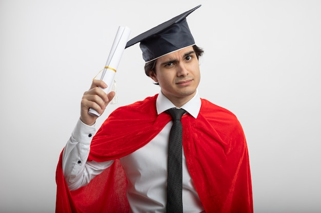 Confident young superhero guy wearing tie and graduate hat raising diploma isolated on white background