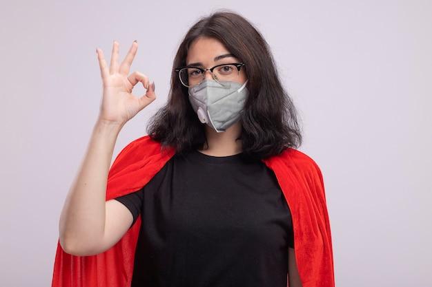 眼鏡と保護マスクを身に着けている赤いマントの自信を持って若いスーパーヒーローの女性は、白い壁に分離されたokサインをやって正面を見て