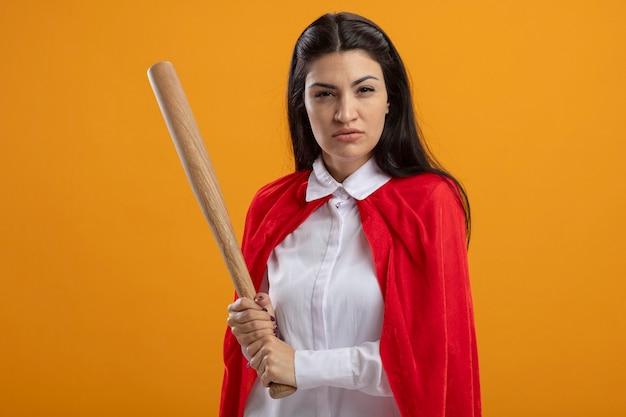 Уверенная молодая суперженщина, держащая бейсбольную биту, смотрящую вперед, изолированную на оранжевой стене