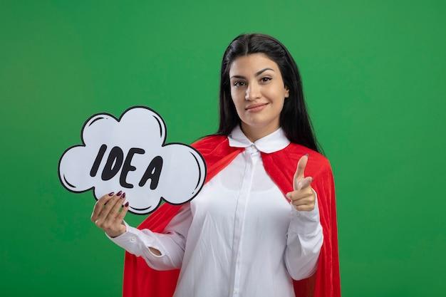 Уверенная молодая суперженщина держит пузырь идеи и указывает указательным пальцем на аудиторию, смотрящую вперед, изолированную на зеленой стене