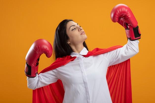 オレンジ色の壁に隔離された彼女の手を見て強いジェスチャーをしているボクシンググローブを身に着けている自信を持って若いスーパーウーマン