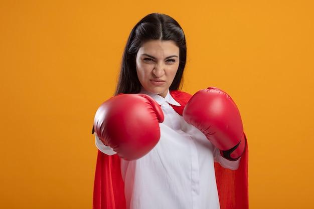 オレンジ色の壁に分離されたボクシングのジェスチャーをしている正面を見てボクシンググローブを身に着けている自信を持って若いスーパーウーマン
