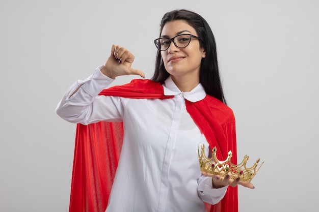 Confident young superwoman wearing glasses holding crown looking at front pointing at herself isolated on white wall