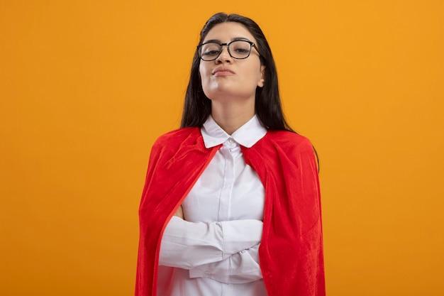 Fiduciosa giovane superdonna con gli occhiali in piedi con la postura chiusa guardando la parte anteriore isolata sulla parete arancione