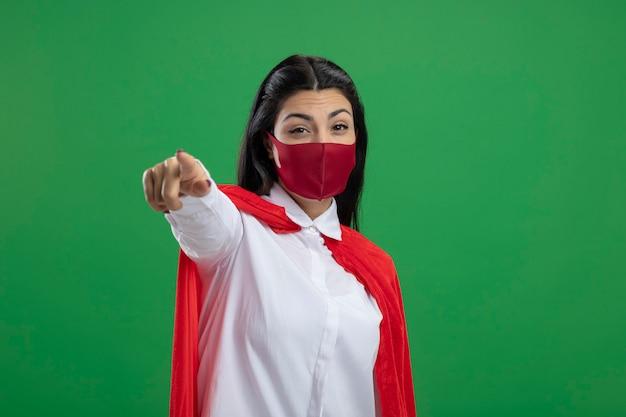 緑の壁に隔離された正面を見て、指しているマスクを身に着けている自信を持って若いスーパーウーマン