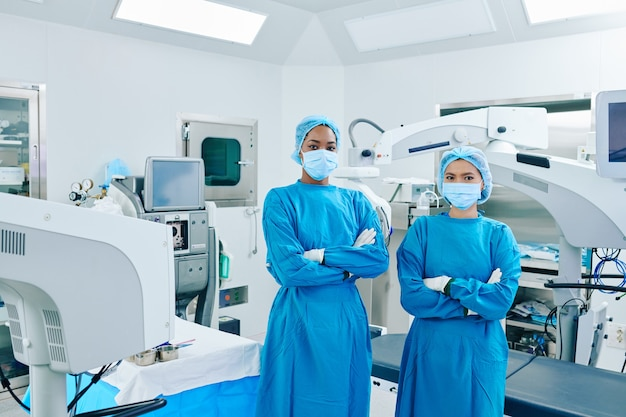 腕を組んで正面を見ながら手術室に立っているスクラブと医療用マスクの自信を持って若い外科医のアシスタント