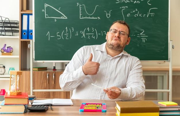 Fiducioso giovane insegnante con gli occhiali seduto alla scrivania con materiale scolastico in aula tenendo il numero di fan guardando davanti mostrando pollice in su