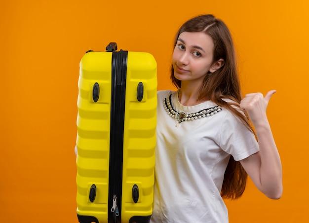 Уверенная молодая девушка-путешественница держит чемодан и указывает на правую сторону изолированного оранжевого пространства