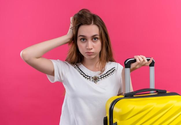 Уверенная молодая девушка-путешественница держит чемодан и кладет руку на голову на изолированном розовом пространстве